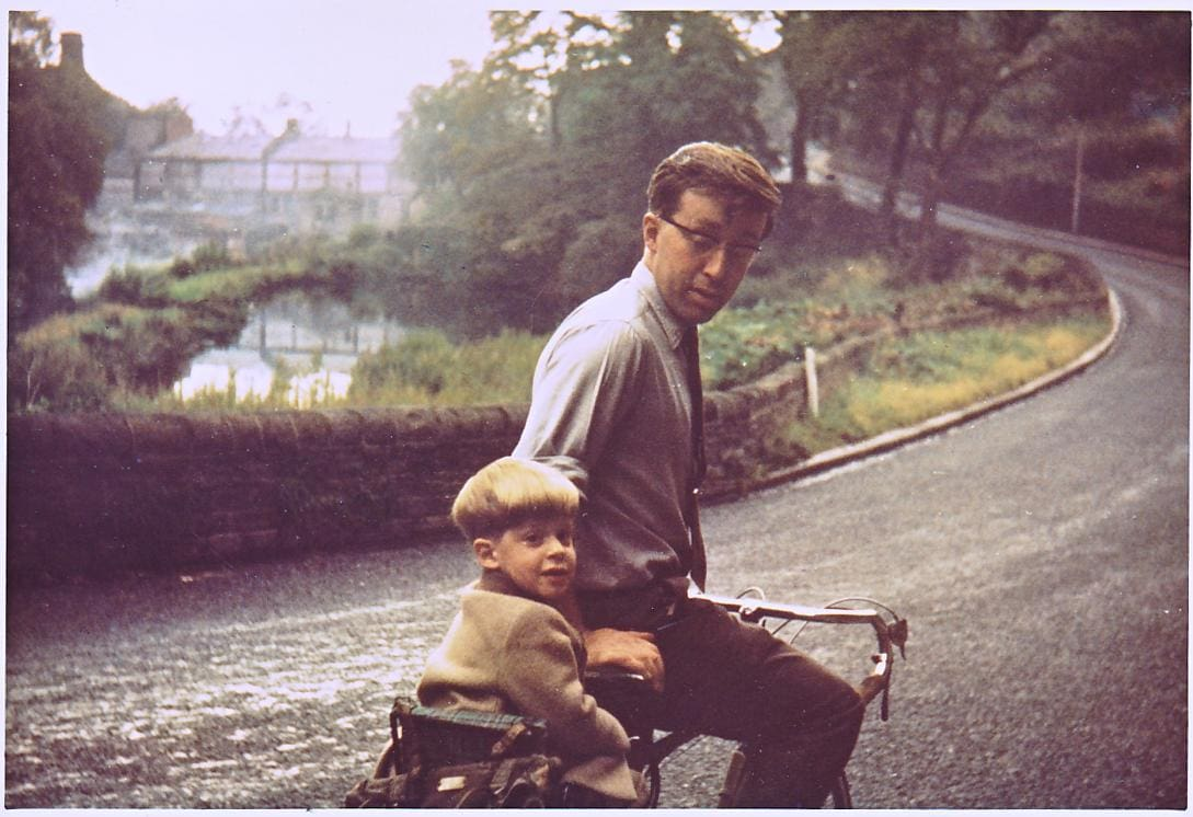 """My earliest cycling days, with Dad doing all the work. December 1964. Bikes had only just been invented, so clearly no one had ever needed helmets or thought of any aspect of child safety yet."""