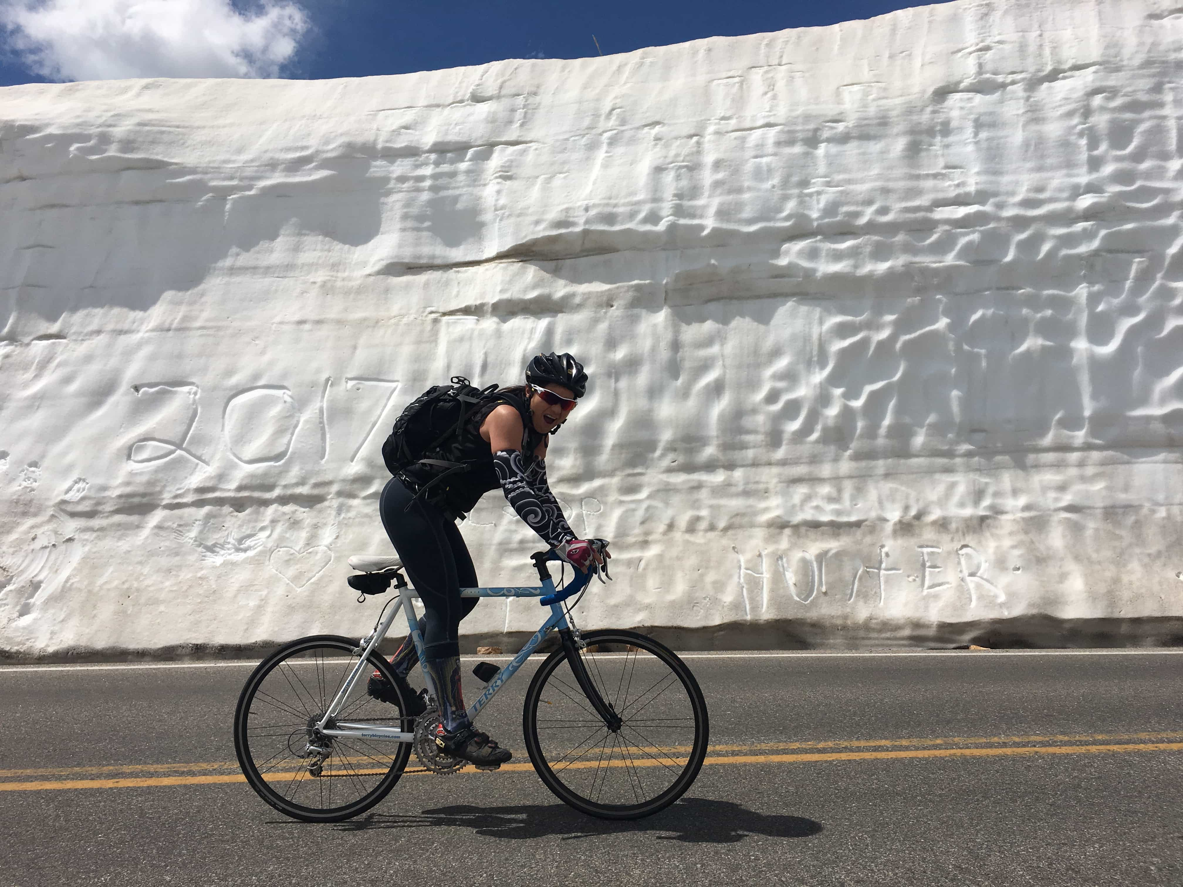 Cyclist riding on a Terry bicycle next to a wall of packed snow or exposed glacier along a road