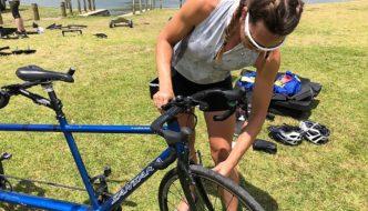 Photo of Joy, Santana Tours bike mechanic, checking brake setup for customer who brought their own tandem on cycling vacation