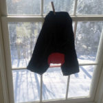 Photo of bike shorts hanging in a sunny window to dry after washing.