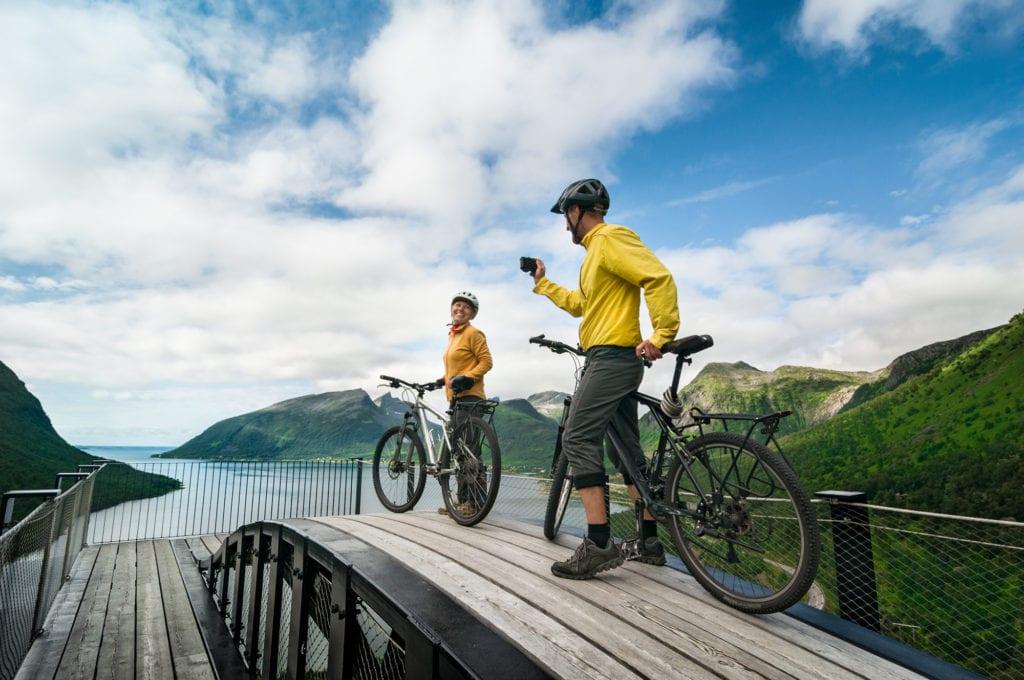 Image of a couple taking photos while enjoying a scenic cycling vacation in Norway