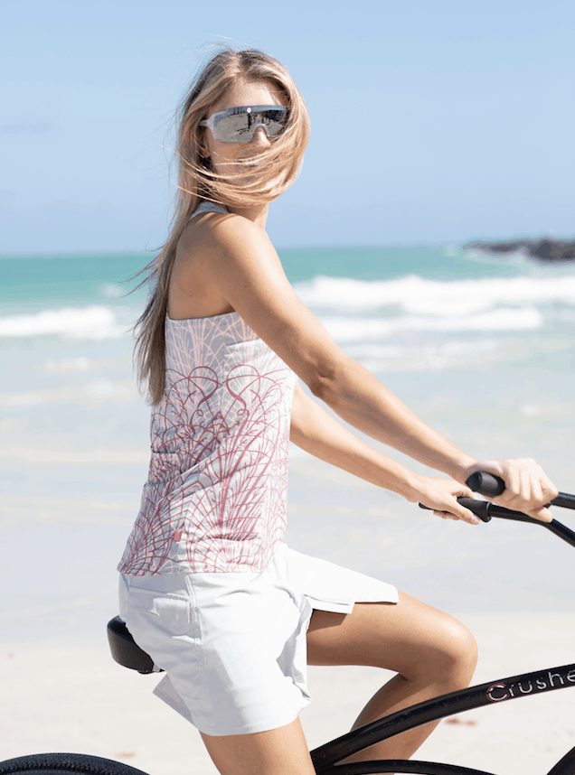 Photo of model riding a cruiser bike on the beach, wearing a Terry Metro Skort Lite in Sand