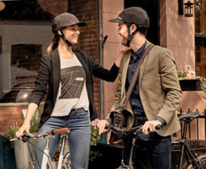 Photo of a man and woman on bicycles, both wearing Park & Diamond baseball cap style Bike Helmets