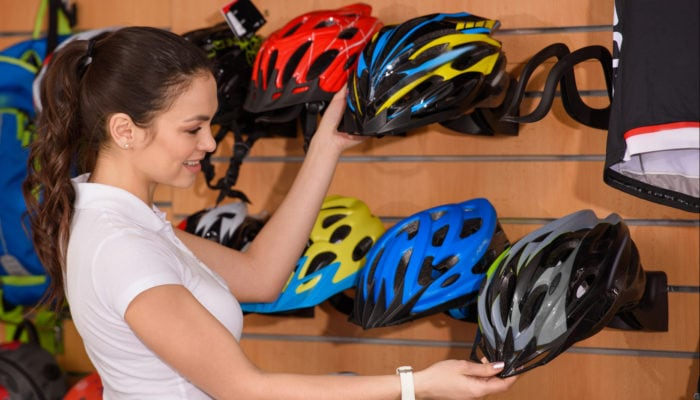 Photo of a woman in bike shop shopping for a bike helmet