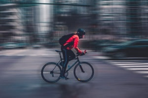 Photo of cyclist wearing bright clothing contrasting with gloomy blurred background of city and traffic