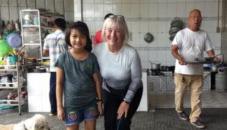 Kate W. a Terry customer wearing the Soleil Long Sleeve Top on a cycling tour in Vietnam, posing with a young girl at an eating place