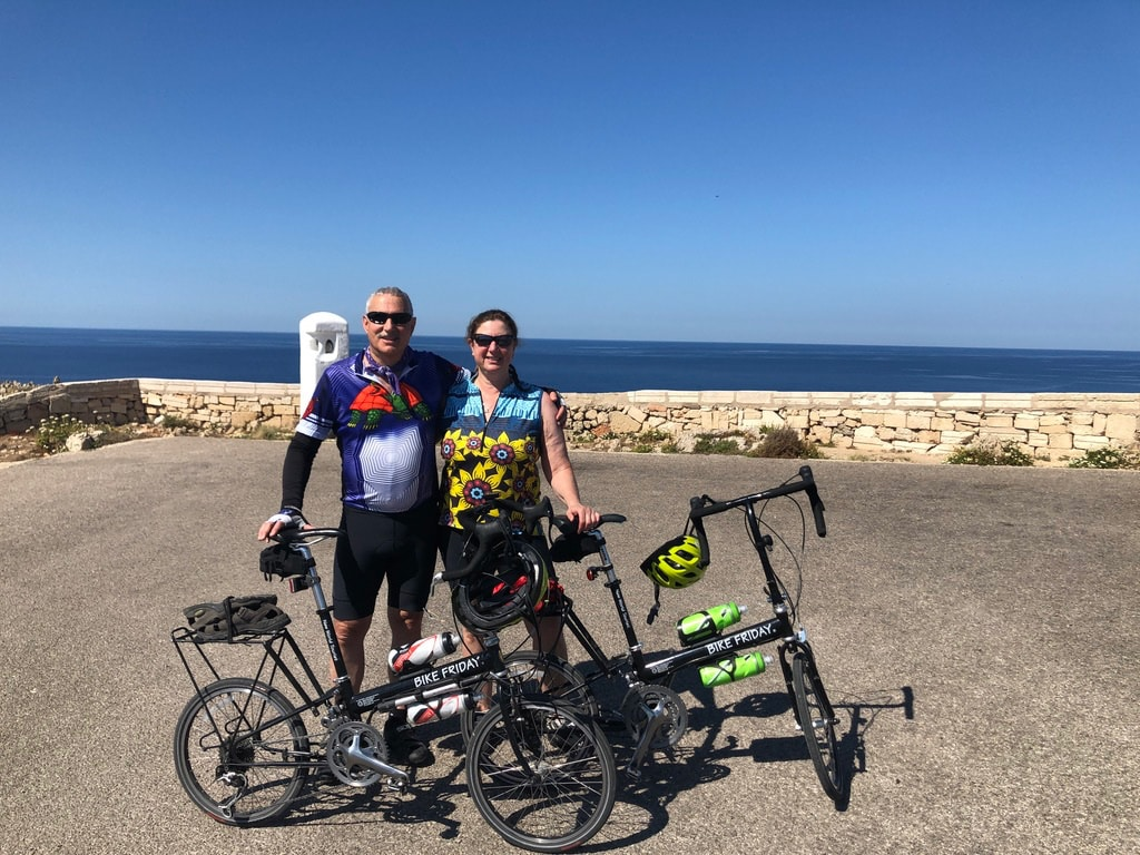 Sylvia W. and companion in hot weather on tour in Minorca, wearing a Terry Breakaway Mesh cycling top in Sunflower Climbers