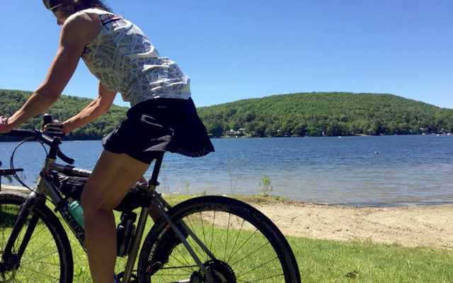 Photo of cyclist Jeannette wearing the Terry Rebel skort while riding past Lake St. Catherine in Vermont's Green Mountains