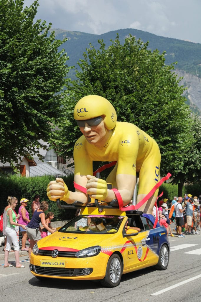 photo of a motorized float in the tour de france caravan, featuring an effigy of the race leader in yellow jersey