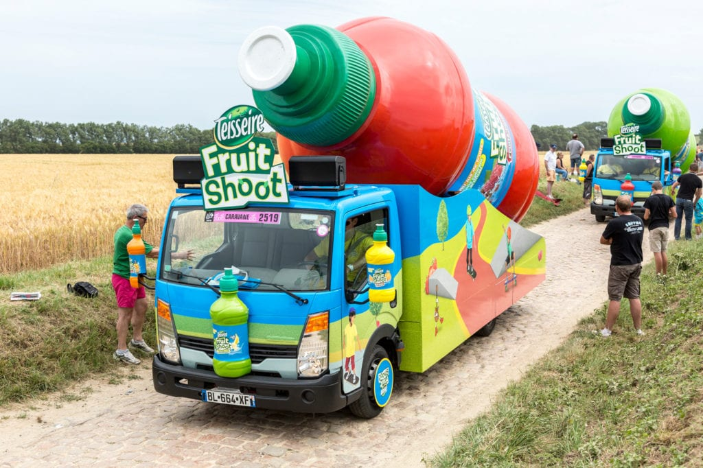 photo of a motorized float in the tour de france caravan, featuring a giant colorful effigy of a fruit juice bottle