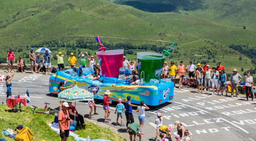 photo of a motorized float in the tour de france caravan, on a mountain road, featuring colorful soft drinks