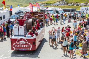 photo of a motorized float in the tour de france caravan, featuring a manufacturer of bread products passing promotional samples to a crowd of campers along the route of a tour de france mountain stage