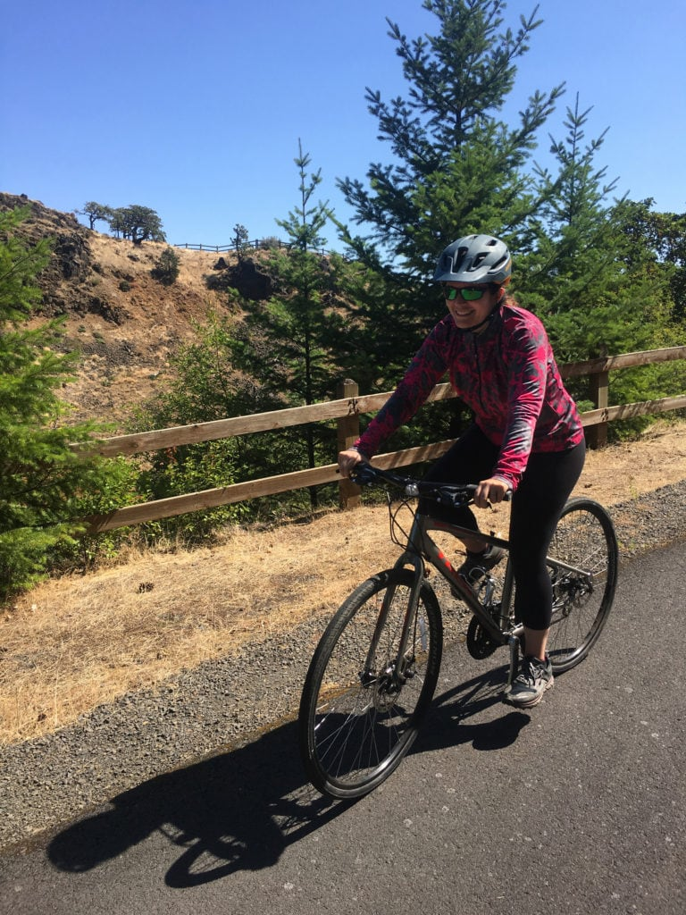 Photo of the author cycling on the Historic Columbia River Highway Trail, past rock outrops and conifers, wearing a Terry Thermal Jersey