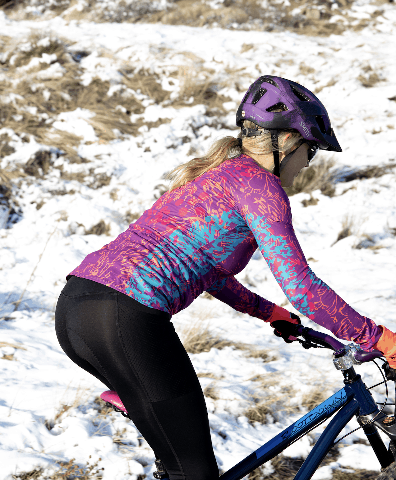 Woman riding a mountain bike in a snowy landscape, wearing Terry cycling top and Thermal cycling tights