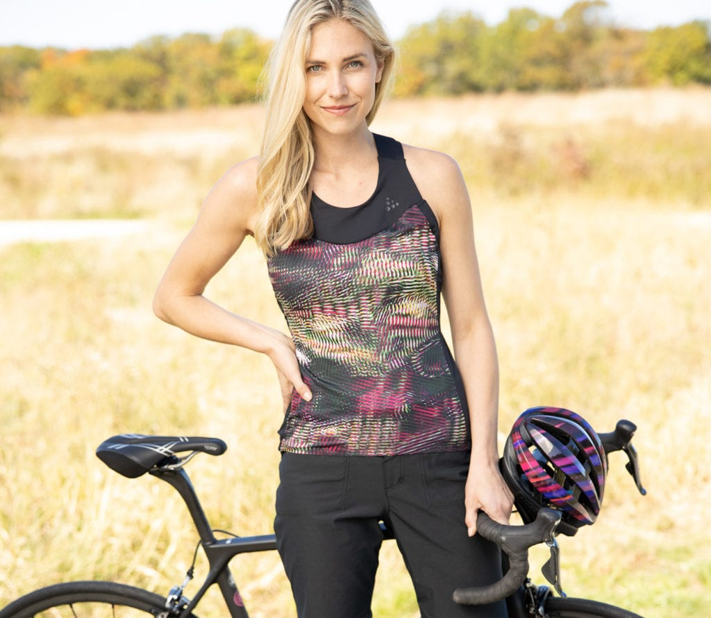 Woman pausing during bike ride through fall fields, holding bicycle mounted with Terry Corta performance bike saddle.