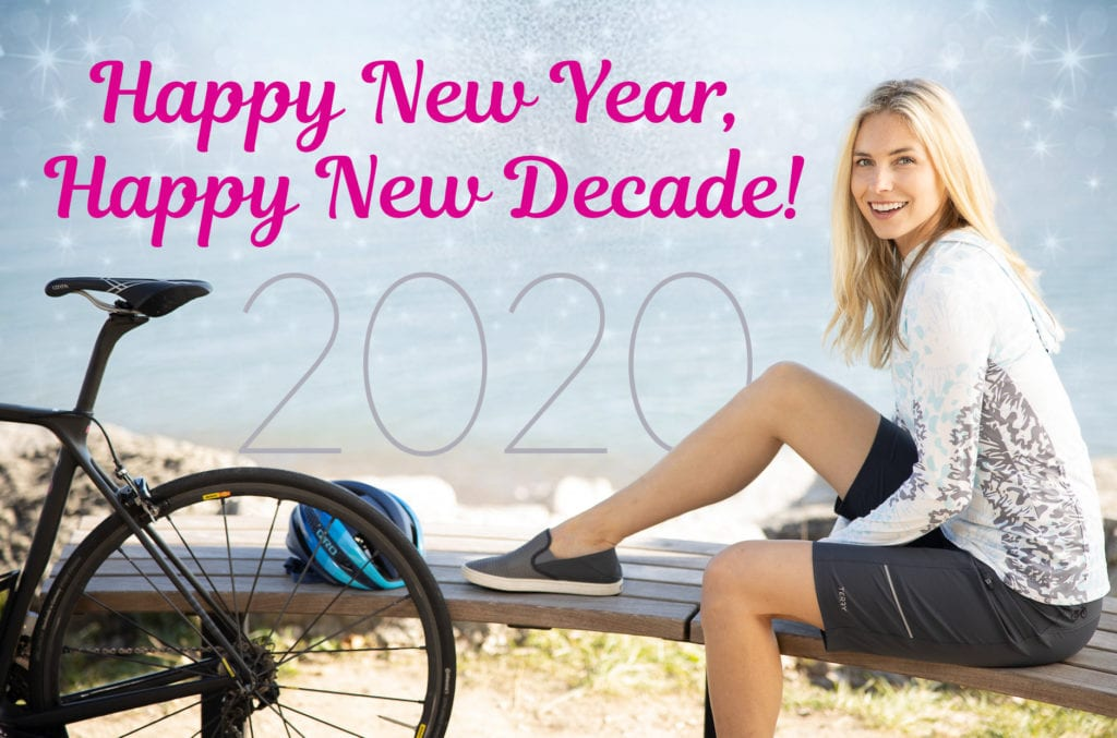 Female cyclist relaxing during a bike ride next to sparkling ocean, text overlay reads Happy New Year, Happy New Decade!