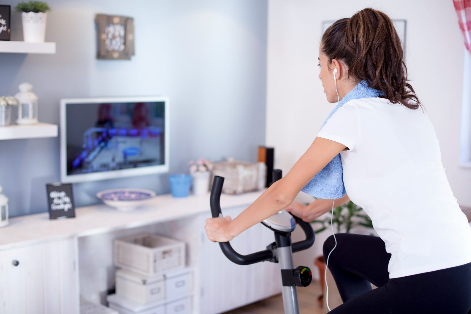 Woman riding a stationary bike at home, watching TV with earbuds
